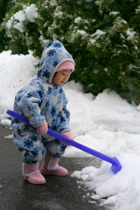 little toddler playing in snow